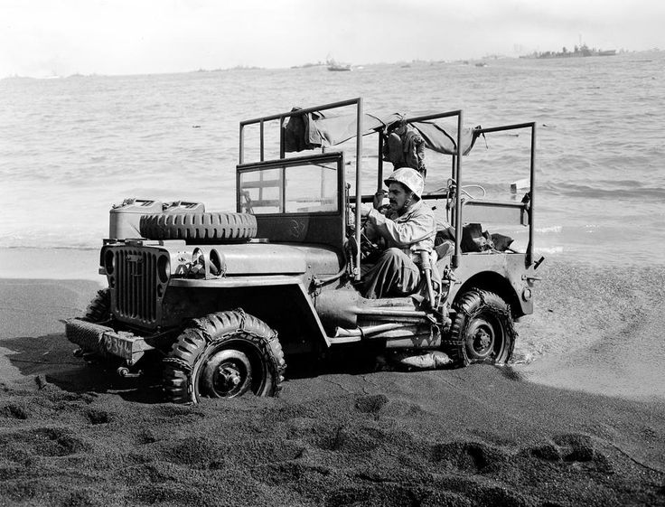 A U.S. Marine ambulance jeep on the sandy beaches of Iwo Jima works its way ashore on Feb 26, 1945.