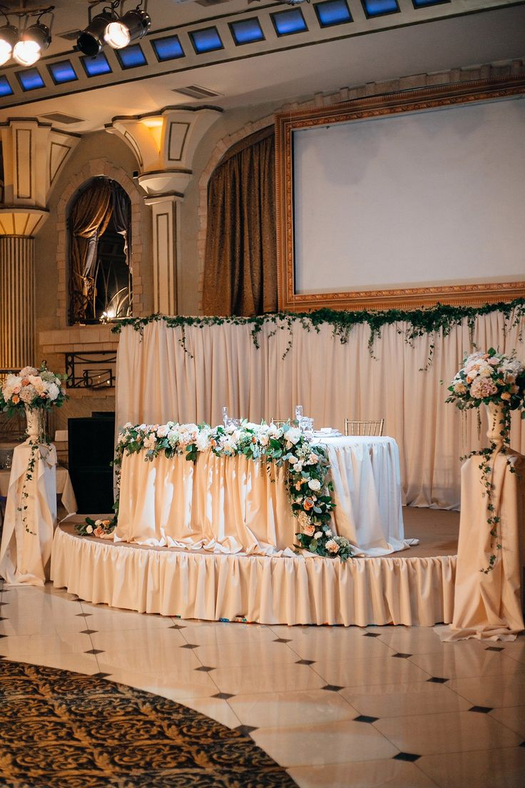 The delicate decor of the presidium is decorated with a peach-colored cloth. A flower garland descends on the table using roses, carnations, hydrangeas, methiol, eucalyptus and salal, and compositions that form the presidium on the sides