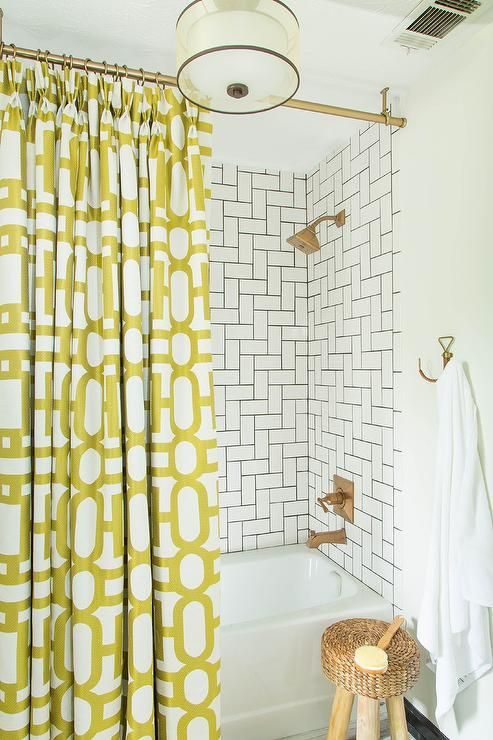 Amazing bathroom features a drop-in tub and shower combo accented with white subway tiles laid out in a geometric pattern with dark grout lined with a Brizo Brilliance Brushed Bronze Tub and Shower Valve Trim Single Handle Pressure Balance with H2Okinetic Technology from the Vesi Collection finished with a yellow geometric shower curtain alongside a round rope stool on three legs under a rope towel hook.