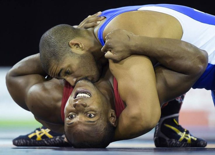 Cuba's Yasmany Lugo, top, pins down Kevin Mejia of Honduras in the men's Greco-Roman wrestling gold medal 98 kg bout during the Pan Am Games in Toronto, Thursday, July 16, 2015. Lugo won the gold medal. (Nathan Denette/The Canadian Press via AP)