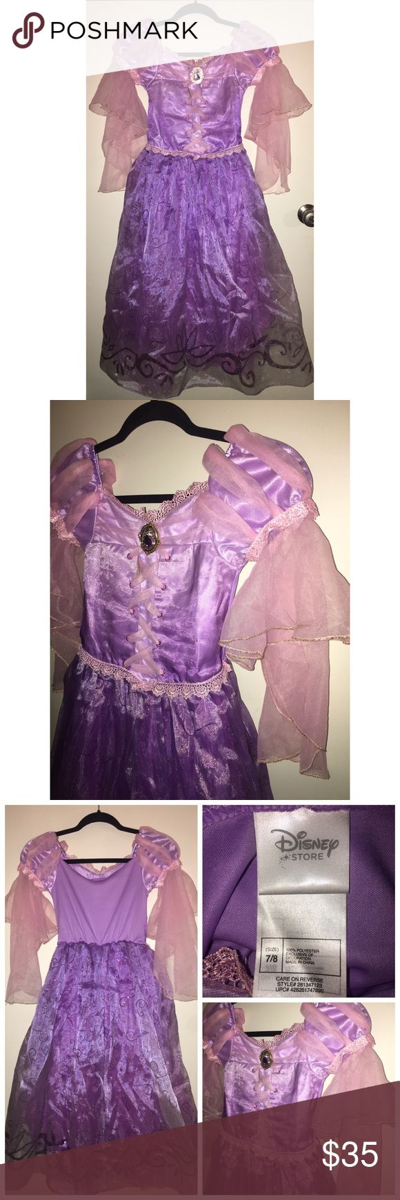 Disney Store Rapunzel Costume Pre•loved Disney Store Rapunzel Costume Size 7/8 Glitter accents and ruffled mesh glitter trim at top and waist Inset panel with faux lace-up satin ribbons over mesh and acetate Paned puff sleeves of satin and golden mesh Long mesh sleeve with ruffled glitter trim at wrist Patterned satin overskirt with glitter-trimmed hem brooch with clear domed cover and jeweled accents Stretch fabric back EUC (keep in mind it's been played in) No stains or rips 9817P Disney…