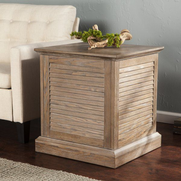 Wave goodbye to clutter and welcome coastal charm into your home with this trunk end table, a versatile addition to your abode that brings fantastic function to any room. Crafted of manufactured wood with laminated ash veneers, this piece features a hinged top that lifts up to reveal ample storage for spare blankets, stacks of magazines, or even shoes. Its louvered sides give this simplistic silhouette a boost of airy appeal, while its weathered, white-limed burnt oak finish lends your…