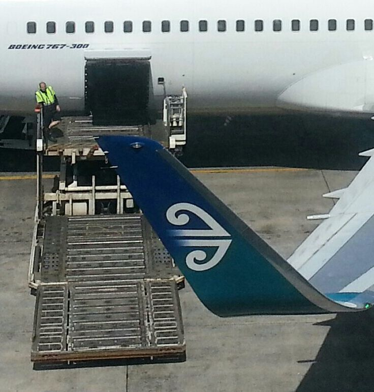 Air New Zealand 767-300 with blended winglets. Container loader waiting for containers