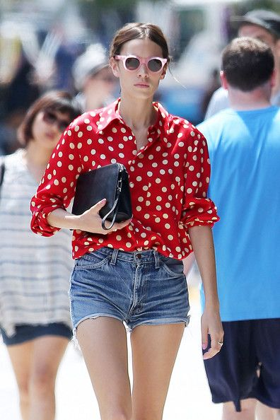 Alexa Chung in a red polka dot blouse and cut off denim shorts