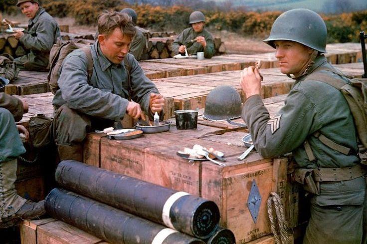 Soldados engenheiros americanos se alimentam usando caixas de munição armazedas para a invasão da Normandia e início da Operação Overlord (Dia D).  Maio de 1944.