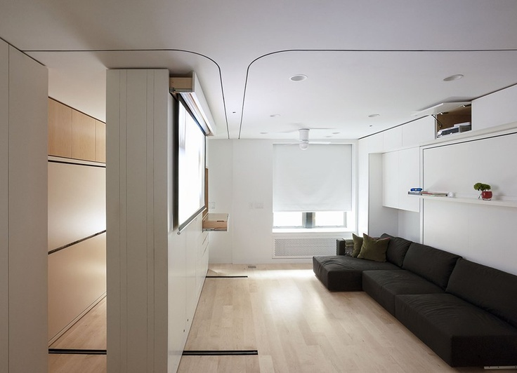 Moveable partition/ cabinet subdivides the room and provides more storage behind. A top drawer provides access to a movie screen.
