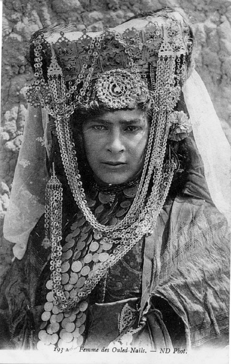Africa | Ouled-Naïls woman, wearing a veil held by a heavily adorned headdress, metal necklaces around her face, large circular medallion on her forehead, coin necklaces, a carnation at her left ear.  Algeria | ©Neurdein frères | ca. 1905 | Scanned old postcard image.