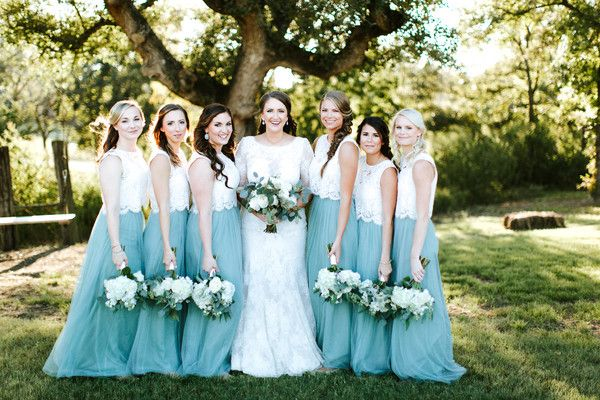 """<strong class='info-row'>Benjamin Garrett Photography</strong> <div class='info-row description'><html> <head></head> <body> Kari's bridesmaids looked fresh and fun-in two piece bridesmaid dresses. The top featured a lace bodice, which paired perfectly with the teal tulle skirt. Venue: <a href=""""https://www.weddingwire.com/reviews/lone-oak-barn-round-rock/02dae14e7197b18e.html"""" target=""""_blank"""">Lone Oak Barn </a> Event Coordinator: <a href=""""https://www.weddingwire"""