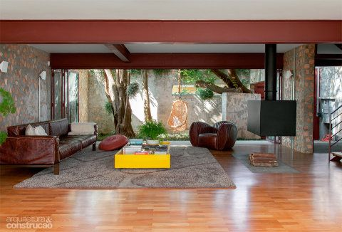 Com a reforma, surgiu este ambiente amplo, que engloba sala de estar, jantar e cozinha – aberto ao jardim da frente (foto) e ao quintal dos fundos. Tacões de cumaru (Assoalhos de Madeira Vitória) forram boa parte do espaço. Projeto do escritório Apiacás Arquitetos.