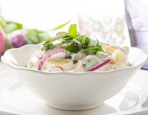 Für den Erdäpfel-Bärlauch-Salat die Erdäpfel weich kochen. Noch heiß schälen, in Scheiben schneiden und in eine Schüssel geben. Sofort mit dem