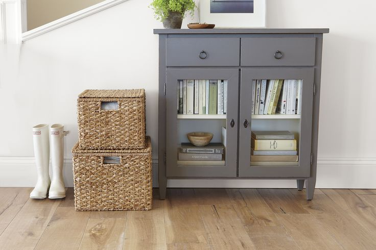 Stretto charms with the clean, casual look of Scandinavian Gustavian furniture. This handcrafted entryway cabinet has custom colors to coat its neat lines in a warm grey opening to an off-white interior behind two glass doors.