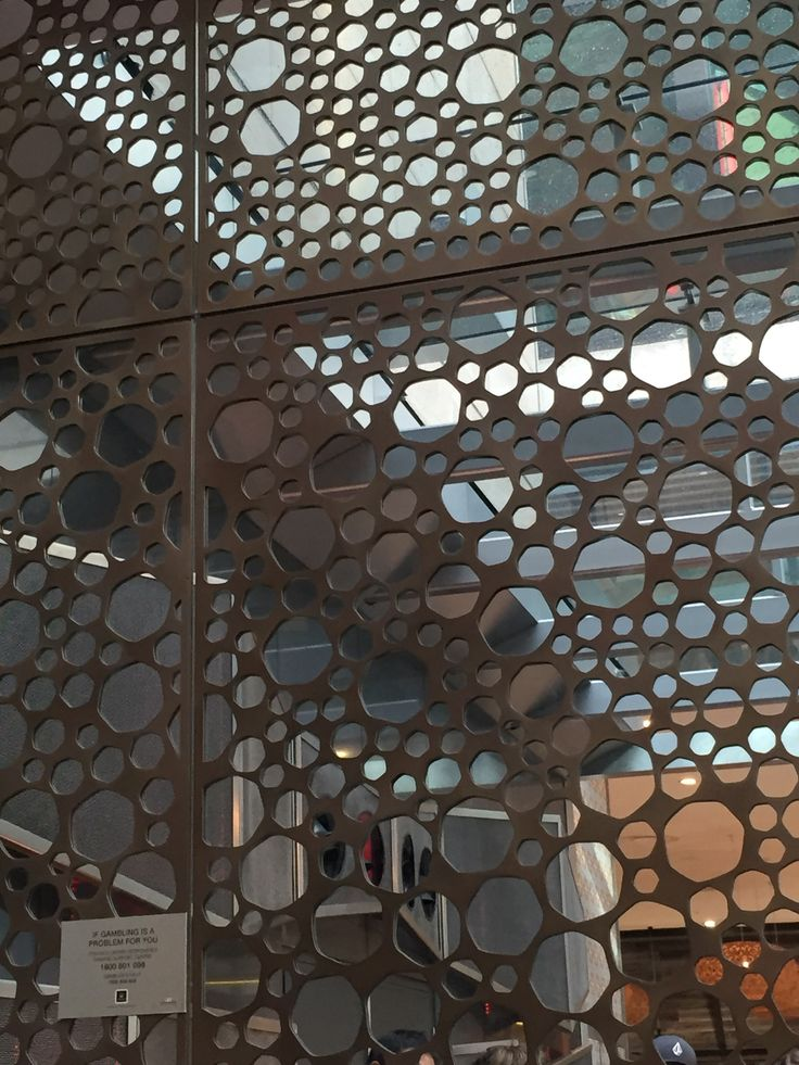 PHOT FIVE: Glass placed behind a metal design. Glass is being used in this interior to create a feature wall, the clear glass helps to  emphasize  the metals circle weldings. Located in the crown plaza, It works well in the interior to great a statement piece.