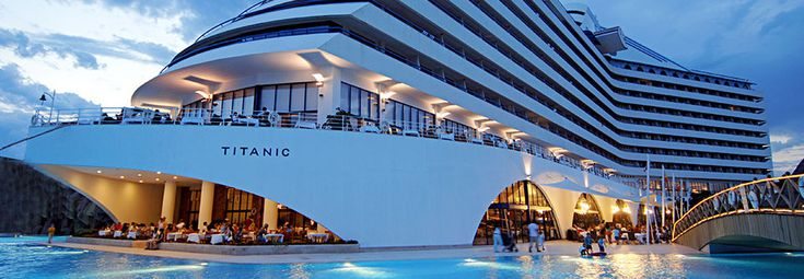"Exterior View of Turkish hotel Titanic Beach Lara. The hotel in Antalya, Turkey, is constructed to be a replica of the doomed ocean liner complete with a lobby inspired by the famous grand staircase and the ""bow"" of the ""ship"" appearing to float in a vast hotel pool."