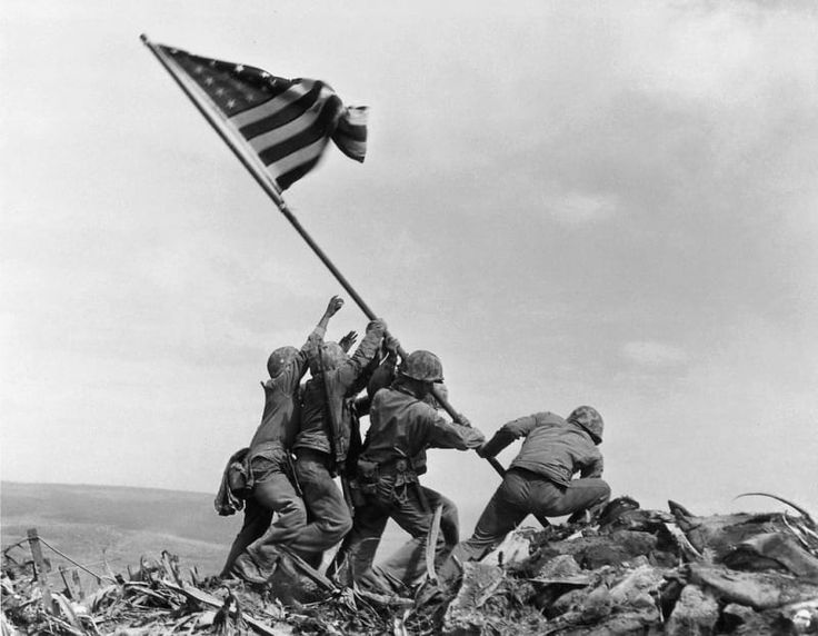 Taken on the island of Iwo Jima, Japan, U.S. Marines and a United States Navy hospital corpsman, raise a U.S. flag atop Mount Suribachi. These men fought alongside more than 70,000 Marines, sailors, and airmen on Iwo Jima, a tiny eight-square-mile speck of volcanic rock and sand midway between Guam and Tokyo, during the closing months of World War II. Three of the Marines depicted in this picture were killed in the following days.