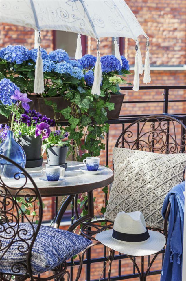 Kaffestund. Bord med mosaikskiva, 3 500 kronor, stol i järnsmide med armstöd, 1 795 kronor, stol utan armstöd, 1595 kronor, pläd, 499 kronor, allt från Spiti. Kaffekoppar med fat från Habitat, 85 kronor styck, Room. Blå vas, 269 kronor, Royaldesign.se. Svarta krukor, 125 och 150 kronor, Designtorget. Beige makramékudde, 399 kronor, Indiska. Blåmönstrad kudde från Habitat, 349 kronor, Room. Parasoll, 1 995 kronor, Love warriors. Blommor från Ginkgo. Hatt privat.