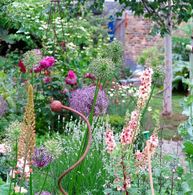 Verticals add texture to a long, thin town garden.
