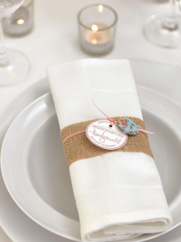 Mit Stoff und hübschen Anhängern ganz einfache weiße Servietten von eurer Location im Handumdrehen zauberhaft als Vintage-Servietten gestalten.