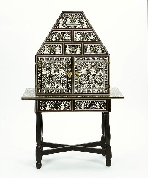 LavishShoestring.com   Cabinet on table-stand Place of origin: Gujarat, India (possibly, made) Sindh, Pakistan (possibly, made) Date: late 16th century-early 17th century (made) Artist/Maker: Unknown (production) Materials and Techniques: Wood, veneered with ebony and inlaid with ivory, with gilt copper mounts and brass carrying handles