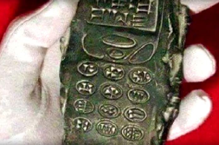 """Nový archeologický """"nález"""" z Rakouska vzbuzuje rozporuplné reakce. Artefakt se velmi podobá mobilním telefonům z 90. let, přičemž jeho »tlačítka« připomínají klínové písmo, které používali staří Su…"""