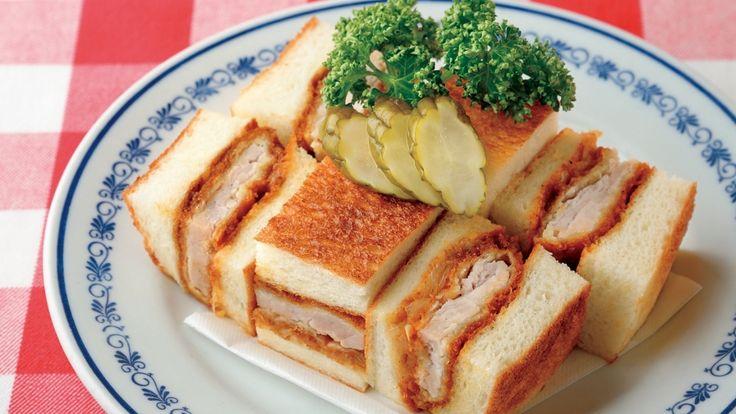 大澤 正季さんの豚ロース肉を使った「ロースカツサンドウィッチ」のレシピページです。ドミグラスソースをからめた本格派のカツサンド。老舗洋食店の人気の味です。 材料: 豚ロース肉、食パン、たまねぎ、卵、マスタード、カツサンド用ソース、ピクルス、パセリ、塩、こしょう、バター、小麦粉、生パン粉、揚げ油