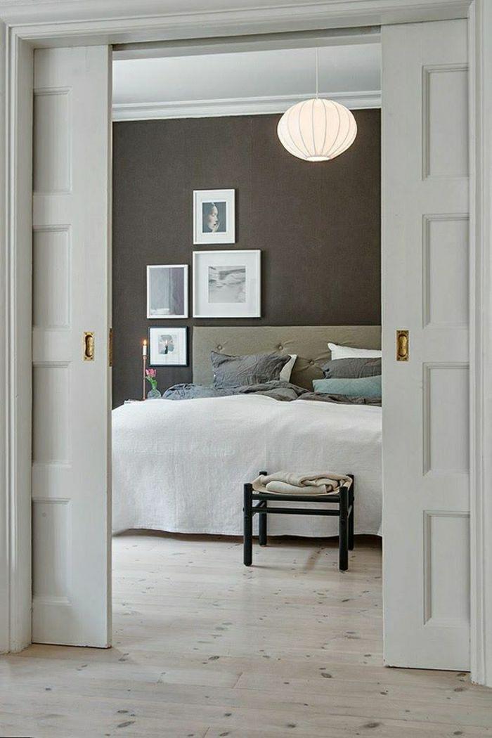 chambre a coucher avec une porte blanche coulissante, lustre boule, mur gris, peinture