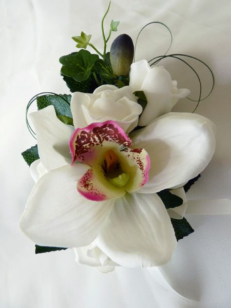 Single, standard size cymbidium orchid with ivory roses and bear grass with an ivory bow trim - perfect for Mother of the Bride or Groom.