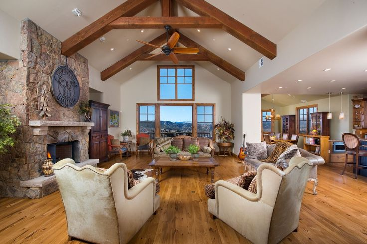 Craftsman Living Room with Hardwood floors, Cement fireplace, Exposed beam, High ceiling, Borra Hairhide Chair, Ceiling fan