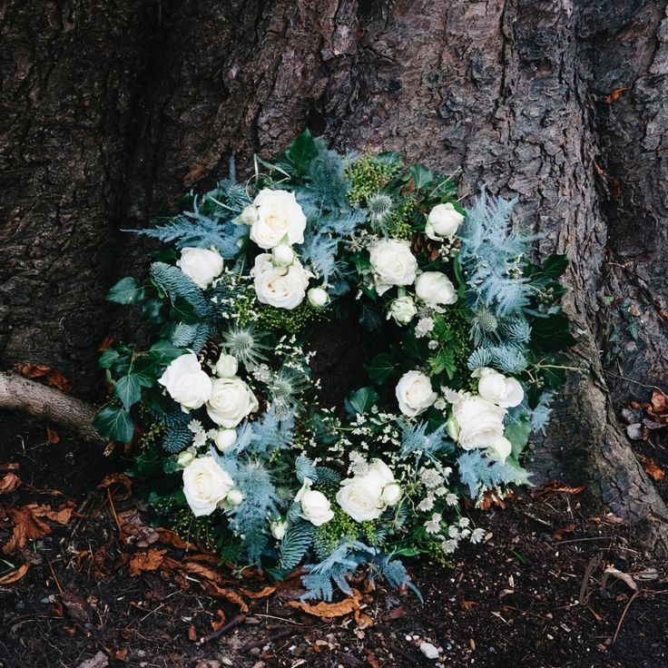 Blue pine floral wreath with white roses and eryngium