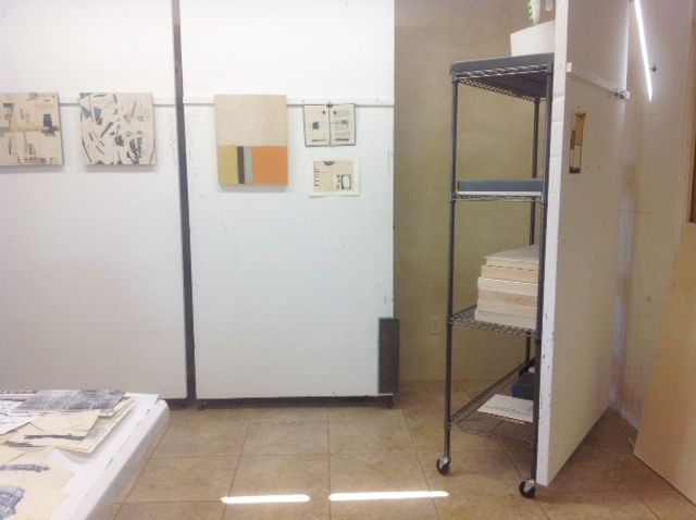 walls for art: white-painted foam insulation board mounted on the backside of metal wheelie shelves from costco...
