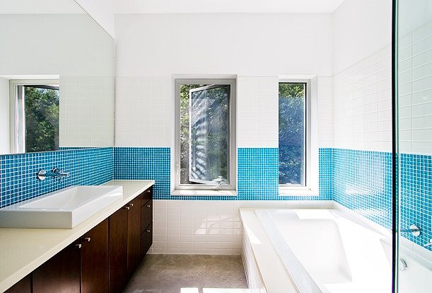 Gananoque Lake Road House - The master bathroom is flooded with natural light and boasts separate soaker tub and glassed-in shower.  The bright blue mosaic tiles give a punch of colour.