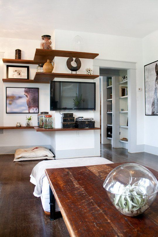 How to Keep a TV from Standing Out Like a Sore Thumb - I LOVE this idea! With the great shelving that follows the angles of the wall; awesome idea!