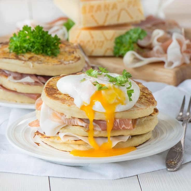 A stack of Grana Padano cheese pancakes, layered with Prosciutto di San Daniele and topped with a poached egg with the yolk running down the side.