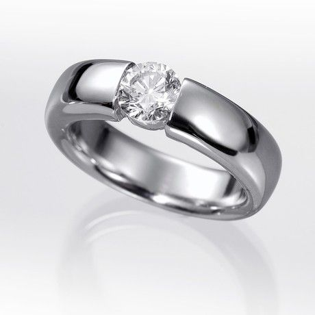 Anillo solitario de diamantes BUDA  Anillo solitario con diamante central talla brillante engastado en una montura de oro de 18 kilates o platino fino con brazos en volumen.