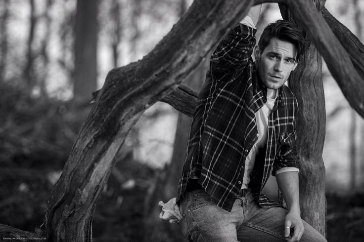 Male model in outdoorsman attire, check shirt, denims and logger boots, sitting amongst the branches of a fallen tree.