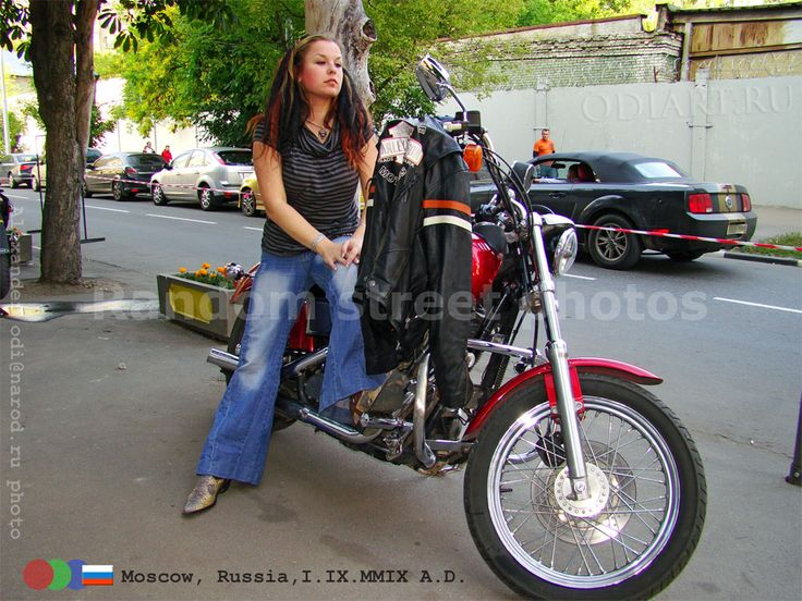 Russian bikers. Moscow, Russia, September 2009 year. Women's flared jeans and a motorcycle jacket and a proprietary Harley Davidson. The girl in blue jeans. Alexander odigif@gmail.com Author's photo.
