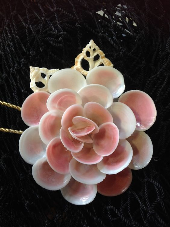 """Seashells handmade into this gorgeous shell flower. All Naturally colorfull shells. A Beautiful Ornament to treasure. This ornament comes in 2 Sizes - small Is between 2""""-3"""" inches large is between 3"""""""