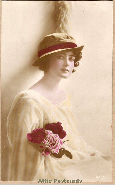 Real photo coloured postcard of a young woman in a yellow dress and hat. Printed in France.