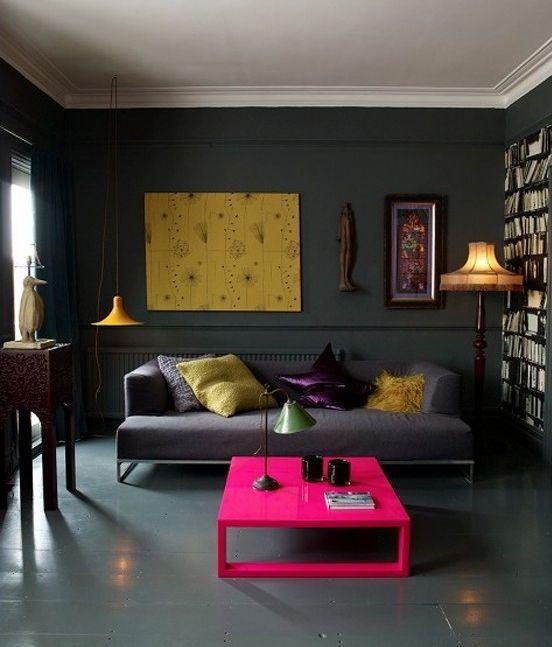 Fluo interieur - een donkergrijze basis krijgt hier een heel hip sfeertje met de fluoroze salontafel en het gele kunstwerk.