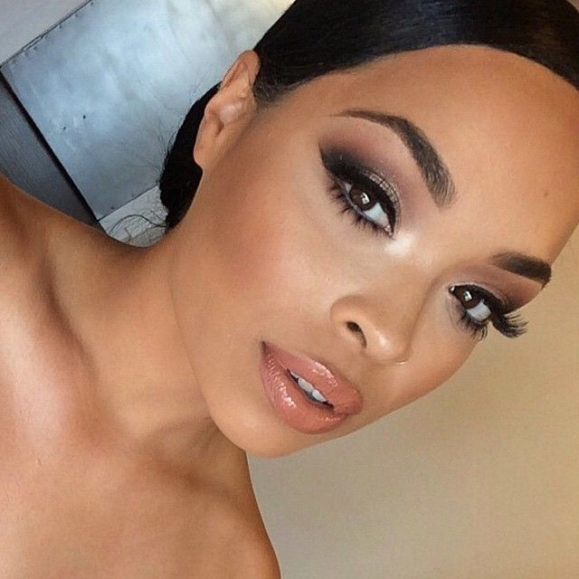 bridal makeup for brown skin with a peachy coral lip, false lashes on top and bottom, with a slightly smokey eye