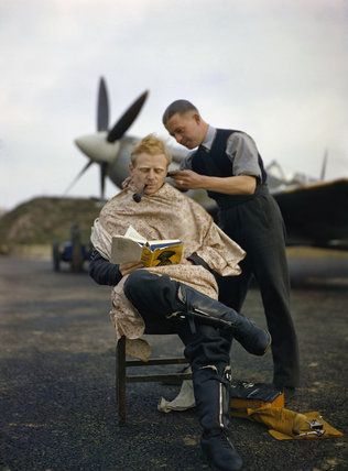 Royal Air Force official photographer -- A pilot at Fairlop airfield in Essex has a haircut during a break between sweeps. A Supermarine Spitfire is in the background. -- High quality art prints, canvases -- Imperial War Museum Prints