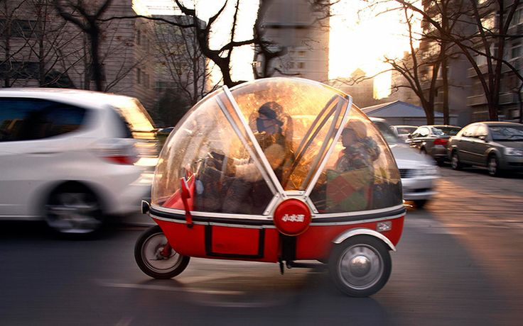 Beijing, China: A woman and her son sit in the capsule of an electric tricycle as they drive along a main road