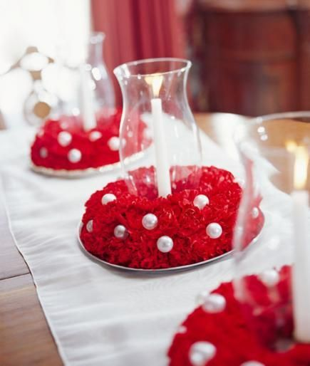 "Encircle glass hurricanes with carnation ""wreaths"" for a pretty Christmas tabletop. More Christmas centerpieces: http://www.midwestliving.com/homes/seasonal-decorating/easy-christmas-centerpiece-ideas/?page=39,0"
