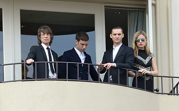 Mick Jagger and his children James Jagger, Gabriel Jagger, and Georgia May Jagger are seen on the balcony of his hotel suite in Beverly Hills before the funeral of L'Wren Scott