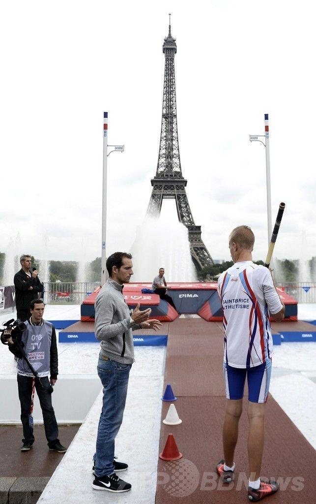 パリ(Paris)のエッフェル塔(Eiffel Tower)前で開催された棒高跳びのイベントで、男性を指導する世界記録保持者のルノー・ラビレニ(Renaud Lavillenie、2014年6月28日撮影)。(c)AFP/STEPHANE DE SAKUTIN ▼29Jun2014AFP|エッフェル塔前で華麗な跳躍、世界記録保持者のラビレニ http://www.afpbb.com/articles/-/3019099 #Renaud_Lavillenie #Eiffel_Tower