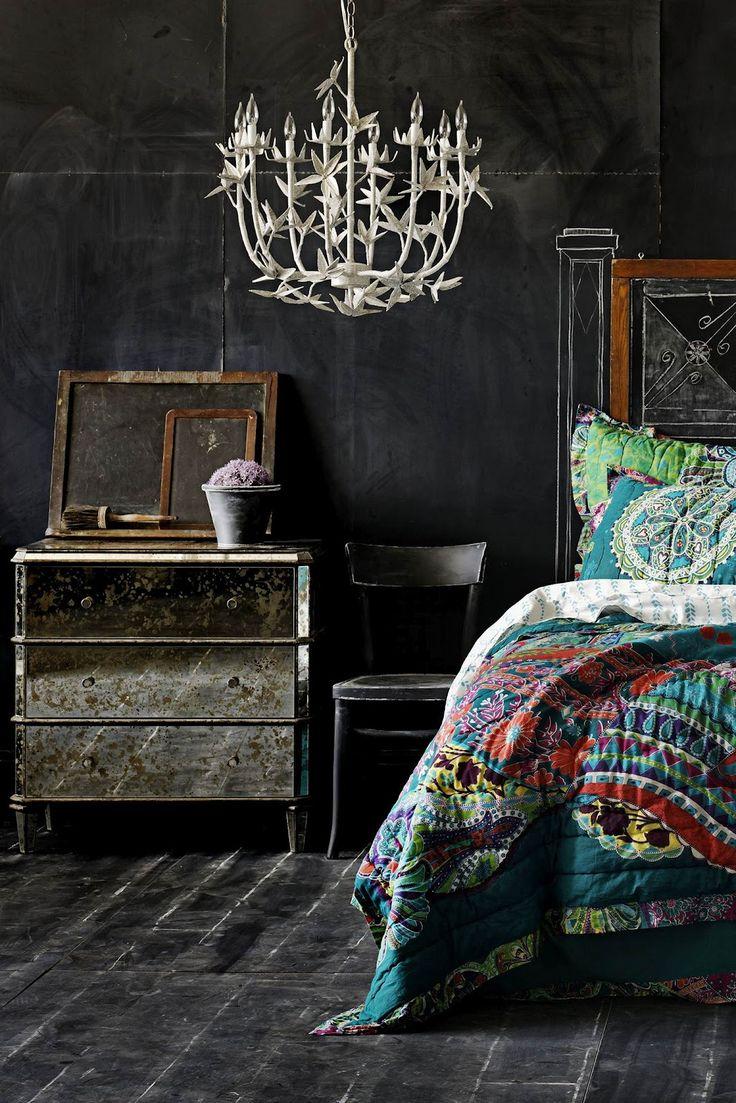 chandelier. chalkboard walls. dark floors. colorful comforter. mirrored dresser.