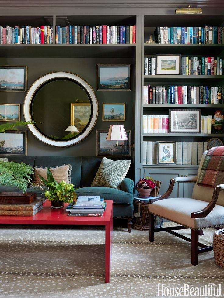 "In the library of Connie Newberry's Dutchess County, New York, house, a sofa covered in Holland & Sherry moleskin blends into the walls. A coffee table from Gerald Bland ""adds the pop of red every room needs,"" Newberry says. Antelope carpet by Stark.   - HouseBeautiful.com"