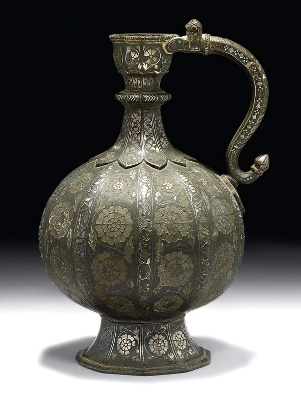 SILVER INLAID BIDRI EWER - India (Deccan, Bidar), 17th century - A bidri ewer inlaid with silver floral designs, the round bulbous and ribbed body rising from a conical splayed foot.