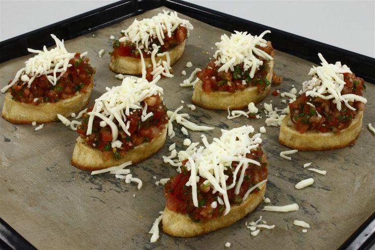 Skær brødet i skiver på ca. 1½ cm og pensl dem med olien. Kom dem i ovnen ca. 5-10 min på 200 grader C. alm. ovn. <BR> <BR> Hak tomater og basilium fint og bland det med presset hvidløg. Lad blandin