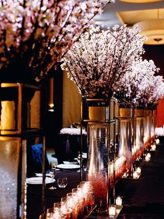 披露宴を盛り上げるドラマティックな会場装花 ダークなクロスに淡いピンクの桜の花を大胆に配したコーディネイト。桜を挿した花器のなかの液体がほんのりピンクに、泡立つようにアレンジされています。たくさん並んだキャンドルの灯りが、ロマンティックな雰囲気を盛り上げて!