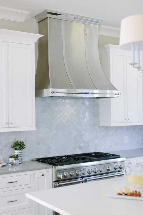 White and gray kitchen features a stainless steel oven range positioned between white shaker cabinets adorning polished nickel pulls and a gray quartz countertop.
